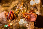 People toasting with champagne with Christmas lights in the background