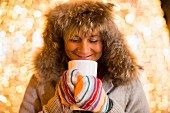 A woman wearing a furry hood and mittens holding a hot drink with Christmas lights in the background