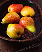 Pears with cinnamon sticks and star anise in a bowl of water