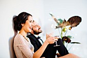 A stylish young couple drinking sparkling wine before a party