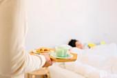 Man serving girlfriend breakfast in bed