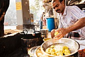 A man eating in a street kitchen (Mumbai, India)