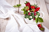 Strawberries with leaves and flowers in a ceramic cup