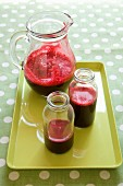 Beetroot juice in bottles and a glass jar