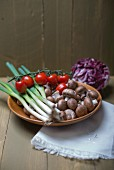 Mushrooms, cherry tomatoes and spring onions in a wooden bowl on a wooden surface