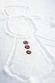 Schneemann in Schnee gezeichnet mit Knöpfen aus Lebkuchenteig