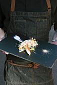 Person hält Servierplatte mit Krabbensalat (Quebec, Kanada)