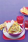 Bunte Knusperecken und rosa Getränk für die Kinderparty