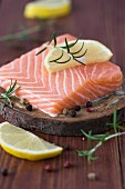 Raw salmon fillet with lemon, rosemary and pepper on a slice of bark
