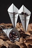 Roast chestnuts in paper cones on autumn leaves