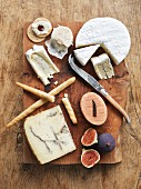Different types of cheese with grissini, crackers and figs