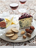 A cheese platter with crackers, nuts, dates and figs