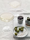 Different types of olive with toothpicks and champagne glasses