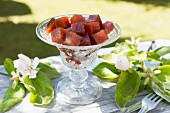 Quince jelly cubes in an old glass bowl on a table outdoors, with quince flowers and branches