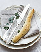 An Easter place setting with dill bread, napkin and cutlery