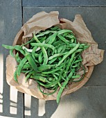 Green beans and okra pods on a piece of paper in a wooden bowl