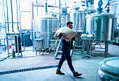 A brewer in a brewery carrying a linen sack over his shoulders (USA)