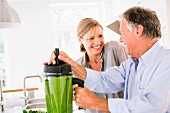 A man and a woman preparing a vegetable smoothie in a kitchen