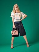 Blonde Frau in Kastenshirt, Hosenrock und Sandaletten
