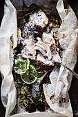 Marinierte Meerbrasse mit Limetten im Pergamentpapier (angebissen)