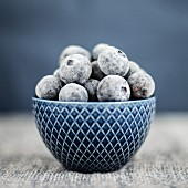Frozen blueberries in a blue bowl (close-up)