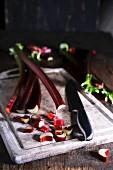 Rhabarber: Stangen und Stücke mit Messer auf Holzbrett
