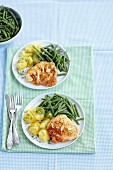 Pork escalope with an onion coating served with potatoes and green beans