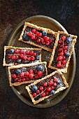 Rectangular tartlets with chocolate, redcurrants and blueberries