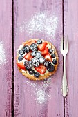 A tartlet with whipped cream and fresh berries