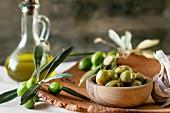 Grüne marinierte Oliven in Olivenholzschüssel, serviert mit frischem Olivenzweig und Olivenöl