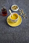 Tasse mit vedischer Milch und Fläschchen mit Ahornsirup und Kardamomkapseln