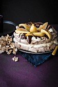 Chocolate pavlova with poached pears, dark chocolate and cream