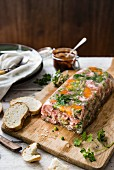 Ham hock terrine on a chopping board with bread and chutney