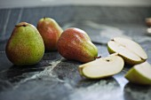 Pears, whole and sliced, on a marble surface