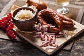 Sausages, sauerkraut and bacon strips on a wooden chopping board