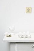 weiße Eier im Eierkarton, Wachteleier und Hahnfigur auf Kommode