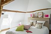 Doppelbett mit beigefarbenem Betthaupt und Ablagefläche in ausgebautem Dachgeschoss mit Gaubenfenster