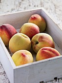 Peaches in a white wooden crate