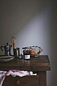 Marmelade, Backutensilien, Teller und Espressokanne auf Holzkommode
