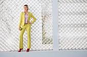 Blonde Frau in gelbem Hosenanzug und roten Sandaletten