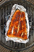 Spiced salmon in aluminium foil on a barbecue