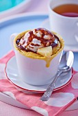 A mug cake with pineapple, a scoop of ice cream and chocolate sauce