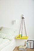 Selbstgefertigte Ablage als Nachttisch mit Kletterseilen an Wand aufgehängt