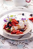 A slice of cheesecake with fresh berries and fruit syrup