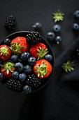 Various berries in a black bowl