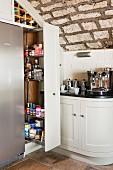 Küchenecke mit offenem, eingebautem Auszugsregal und Flaschenregal unter rustikaler Naturstein-Gewölbedecke