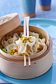 Wontons filled with chicken and pistachio nuts in a steamer basket
