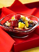 Fruit salad with strawberries, raspberries, blueberries, mango, cashew nuts and acai juice
