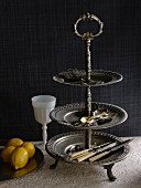 Vintage cutlery on pewter cake stand next to dish of lemons