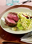 Wild boar steaks on Brussels sprouts leaves with gratinated nectarines